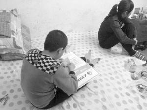 夏俊峰的儿子用一张纸片折一颗心,妻子静静地坐在一边 华商晨报 华商响网首席记者 丛治国 摄