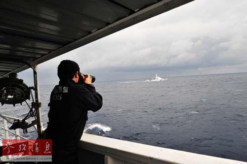 资料图片:2013年2月14日,中国海监执法人员在137船对日方船只进行执法取证。当日,中国海监50、66、137船编队在我国钓鱼岛海域绕岛进行常态化巡航。新华社记者 张建松 摄
