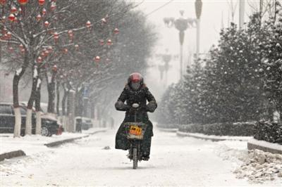 2月5日,山西省介休市,一名行人在风雪中骑行。