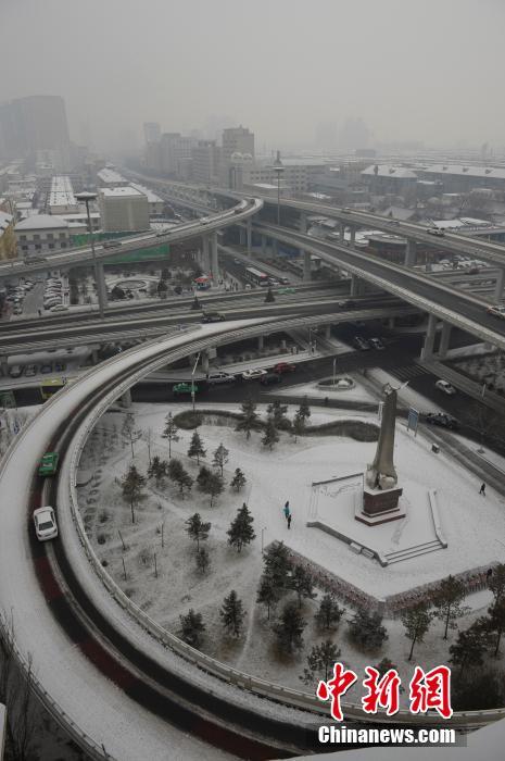 呼和浩特观音寺广场上,市民正在扫雪.当日,呼和浩特降下2014年的图片