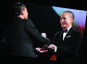 """廖凡(左)从评委梁朝伟手上接过""""银熊奖""""。"""