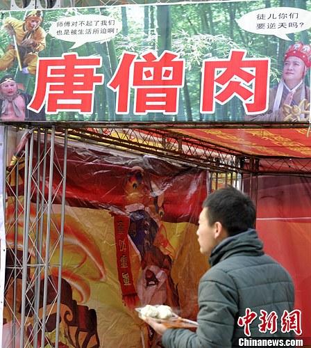 """2月17日,山西太原一小吃摊挂出""""唐僧肉""""雷人广告,画面中的孙悟空、猪八戒与唐僧的对白让人啼笑皆非。中新社发 韦亮 摄"""