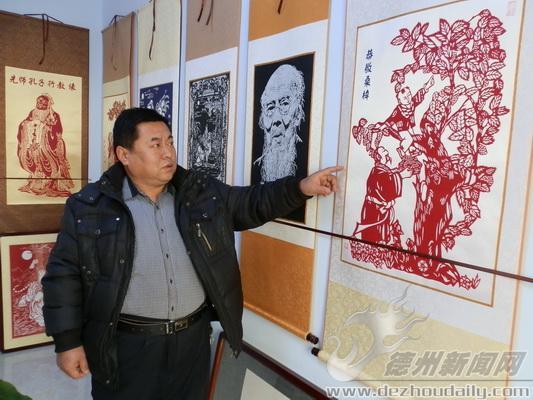 石成才介绍他的剪纸作品.刘平摄图片