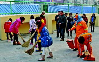 小记者帮助环卫工把垃圾扫到垃圾箱里。
