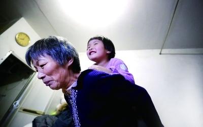 饭后,郭敏总会陪着孩子们玩会儿。对于60岁的她来说,嘉仪还背得动,嘉彬就有些吃力了 摄/法制晚报记者 洪煜