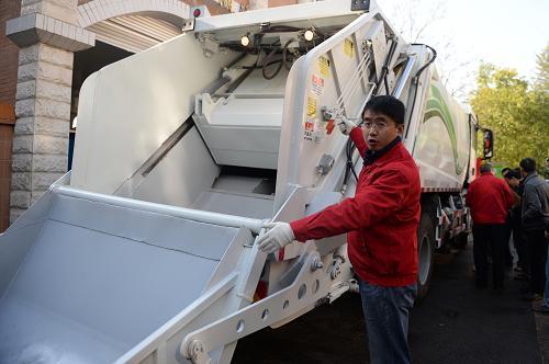 2月21日,在昆明市五华区垃圾中转站,青海洁神装备制造集团有限公司的工作人员介绍LNG环卫车辆的填压垃圾技术。新华社发(胡超 摄)