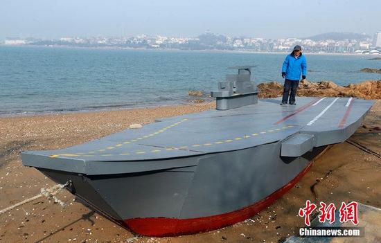 """2014年3月5日,青岛,80岁老人温玉著用一个多月的时间,制造了一艘按照""""辽宁舰""""1:25比例的航母模型,目前这艘航母模型就停放在汇泉路附近的海边。"""