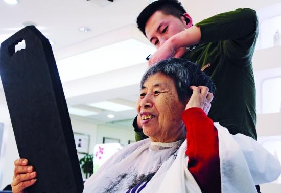 3月8日,呼和浩特市东方名剪理发店的理发师正在为73岁的高大娘理发。自2012年8月起,这家理发店就开始为年满60周岁的老人一元理发,如今已经有5000多名老人享受到了这项服务,5000多元的专项收入也将捐给养老院和福利院。 见习记者 王靖 摄