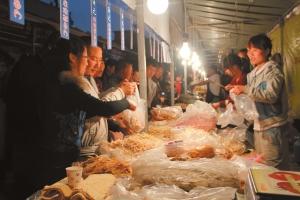 入夜,诱人的美味从小吃街弥漫开来,各个摊点人头攒动。张鸿光/摄