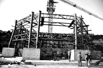 该建筑一二层为方形,三层为圆形,塔吊将大型的钢结构部件运至圆形基座