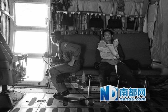 Zulfam y坐在机舱玻璃门旁观察海面。几个小时的搜寻会让人非常疲惫,一名同行记者已经睡着了。