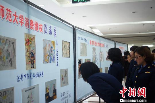 大学生正在参观闽南师范大学消费维权漫画展。 王欣 摄
