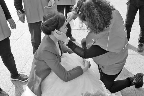 从盘锦远道赶来的爱心志愿者单膝跪地,给孙菊现场化妆。