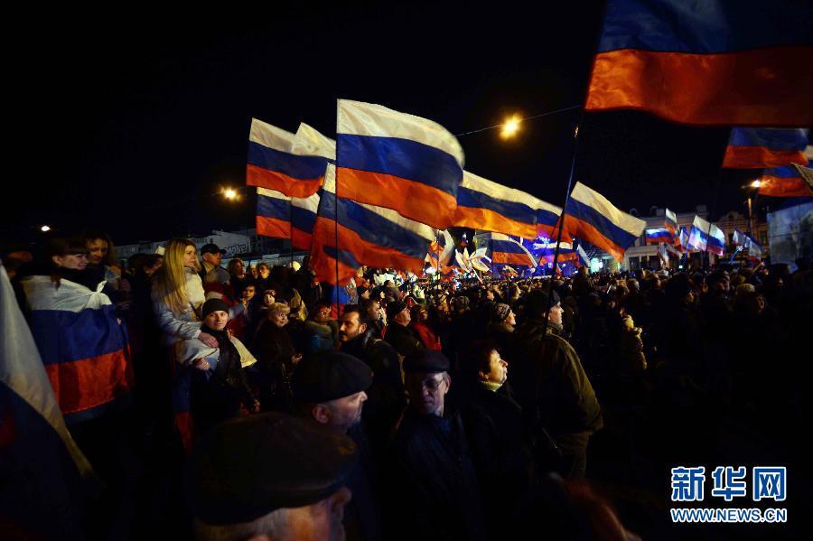 3月16日晚,在乌克兰克里米亚辛菲罗波尔市,人们在克里米亚政府大楼前的列宁广场上手举俄罗斯国旗,参加全民公决庆祝晚会。