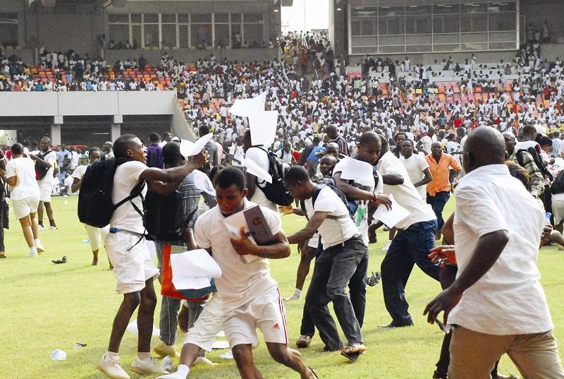 在尼日利亚阿布贾国家体育场,求职者争抢纷飞的考卷