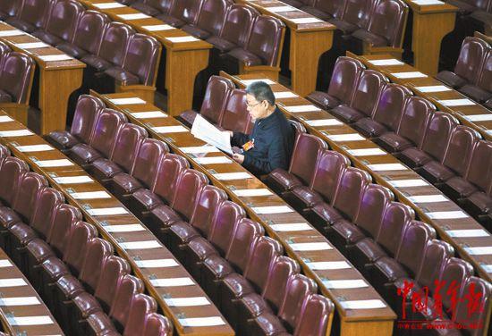 3月12日,全国政协十二届二次会议在北京人民大会堂举行闭幕会,一位早早进入会场的全国政协委员仔细翻阅当天的会议文件。本报记者郑萍萍摄