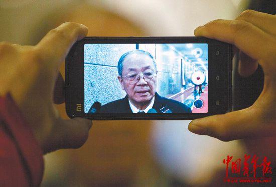 3月10日,全国政协委员尹卓接受媒体采访,一位记者用手机拍摄。本报记者郑萍萍摄