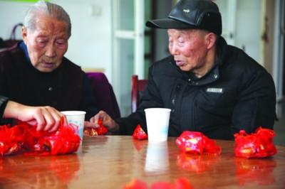 昨日上午,包河区义城街道敬老院的小食堂外响起阵阵鞭炮声,在人们掌声中,82岁的李召海牵着96岁的新娘王志珍走到前台。