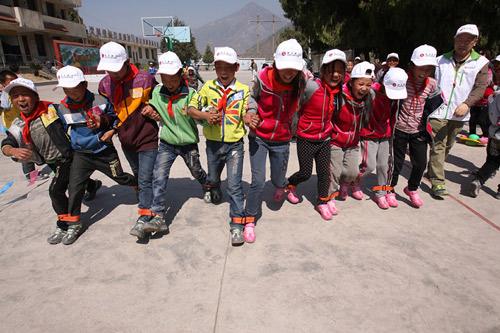 孩子们穿上新鞋与志愿者一起做游戏。