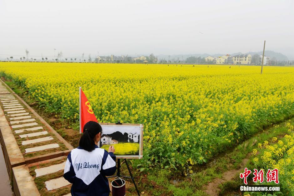 """3月21日,湖南安仁第六届油菜花节在安仁稻田公园举行。在公园内的油菜花地里,一只黄色大""""福鸭""""与""""福蛋""""的亮相吸引了众多游客驻足观看。杨华峰 摄"""