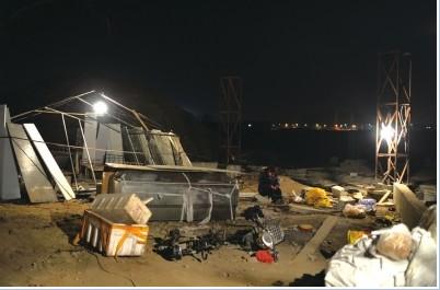 昨晚,装有死者遗体的冰棺搁置在现场,家属在一旁默默守着。京华时报记者王苡萱摄