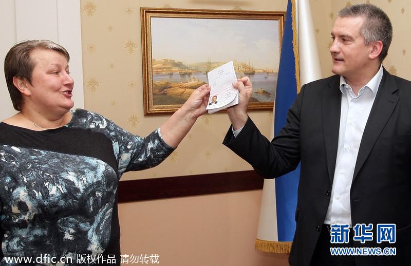 当地时间2014年3月20日,克里米亚辛菲罗波尔,克里米亚总理阿克肖诺夫正在展示新入手的俄罗斯护照。据悉俄当局正式给克里米亚居民颁发护照,民众蜂拥而至排队申请。东方IC供图