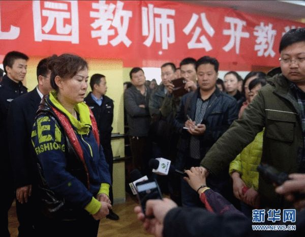 3月25日,幼儿园管理人员(前左)就喂药事件向家长解释。