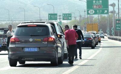 村导正在询问堵在路上的游客。京华时报记者