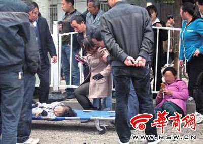 昨日上午11时许,过往的市民积极参与救助,将伤者抬上救护车 本报记者 赵雷