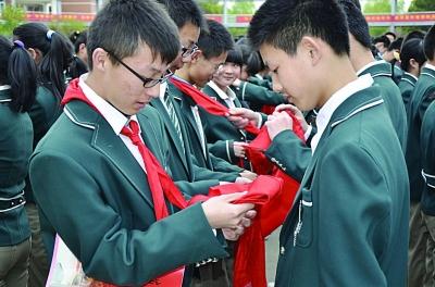 """南师附中江宁分校学生在""""青春仪式""""上,解下陪伴了六年的红领巾。学校供图"""