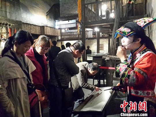 图为羌族姑娘为全国百余家旅行社老总讲解北川震后新旅游。 曾云 摄