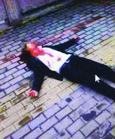 图片上是一名男子躺在地上,头部的鲜血染红了地板