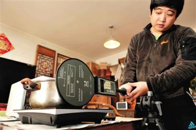 3月31日,实验人员在测试电磁炉磁感应值。新京报记者 秦斌 摄