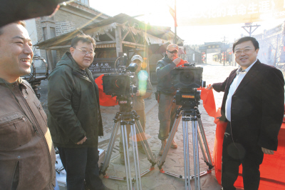 """编剧郝岩(左)、摄影黄伟(左三)与总制片人吴毅(右)一起揭起""""红盖头""""。"""