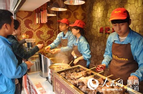 创业者张立洋(右一)跟他的小伙伴在卖鱿鱼 张龙 摄