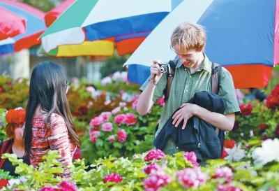 王城公园内,一名外国游客正在给朋友照相留影。