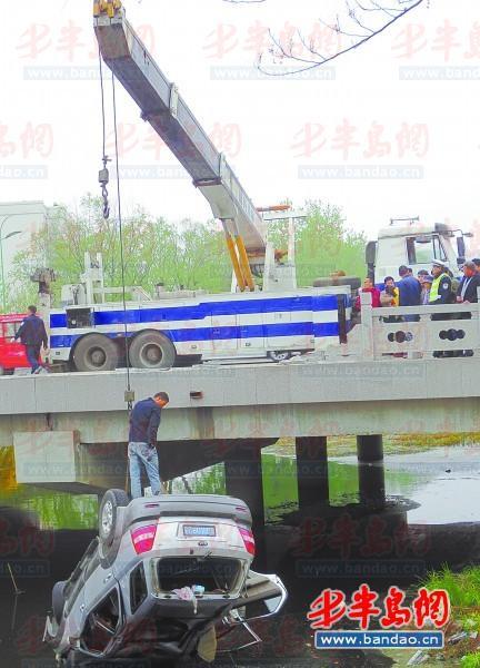 营子河桥上,清障车正努力将轿车吊上岸.