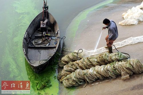 资料图:2013年10月2日,在安徽合肥十五里河入巢湖口处,一名渔民在用高压水枪冲洗被蓝藻污染的渔网。新华社发(杨晓原 摄)