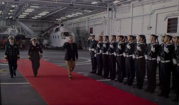 新华网图片:2014年4月7日,美国国防部长哈格尔飞抵青岛,第一时间参观了中国海军航母辽宁舰。图为哈格尔在辽宁舰机库内检阅海军仪仗队。其身后为歼15舰载战机与舰载型直八直升机(疑似为模型机)。