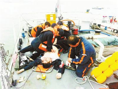 救援人员对一名获救人员进行着紧急救治