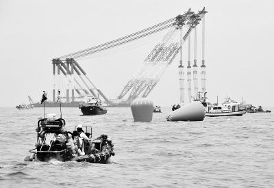 """4月18日,在韩国珍岛附近海域,一架巨型海上起重机在标记""""岁月""""号失事客轮沉没地的浮标附近作业。新华/法新"""