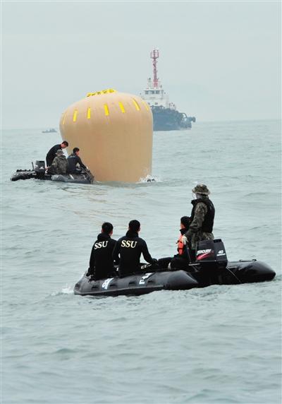 18日,搜救人员准备将气囊捆绑到沉没客轮上。