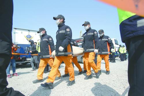 图为21日打捞出的遇难者遗体被救援人员抬走。