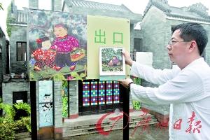 胡锦雄展示自己的画作,园区所用画作确实与其原作一模一样。