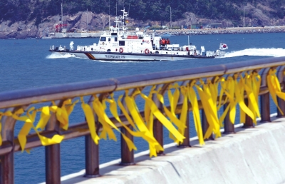 4月24日,在韩国珍岛,祈祷失踪乘客平安返回的黄丝带系在海边护栏上。新华社发