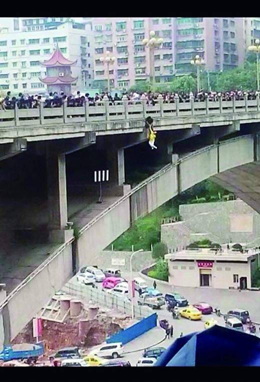 男子单手拉住跳桥女 两人悬在数十米高护栏外(图)