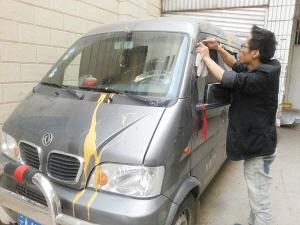 车主费力地清除车上的油漆