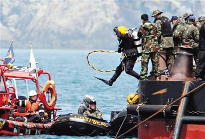"""25日,一名潜水员跳入水中搜寻。对""""岁月""""号的客舱的搜救已经进行了9天,但至今未发现幸存者。"""