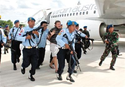 25日,全副武装的军警押走在客机上耍酒疯的乘客。