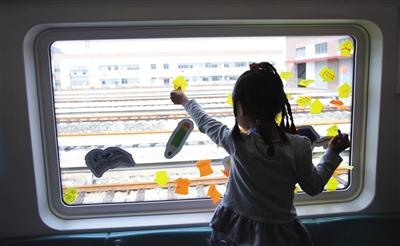 前日,儿童大学专列上,一名小女孩将关于地铁的问题写在纸签上后,贴到车窗上。